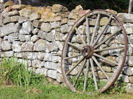 Ein Wagenrad als Gartendekoration - Steinmauer